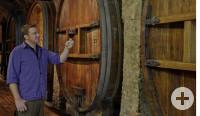 Winzer mit Weinglas im Weinkeller vor Holzfass
